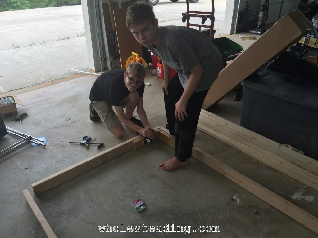 Canaan and Noble assembling the bottom frame. They are using clamps to attached a 90 degree guide to each corner before we drove the screws in. We started by making sure the distance from corner to corner was equal and then used teh guides to help keep the wood in position during the fastening