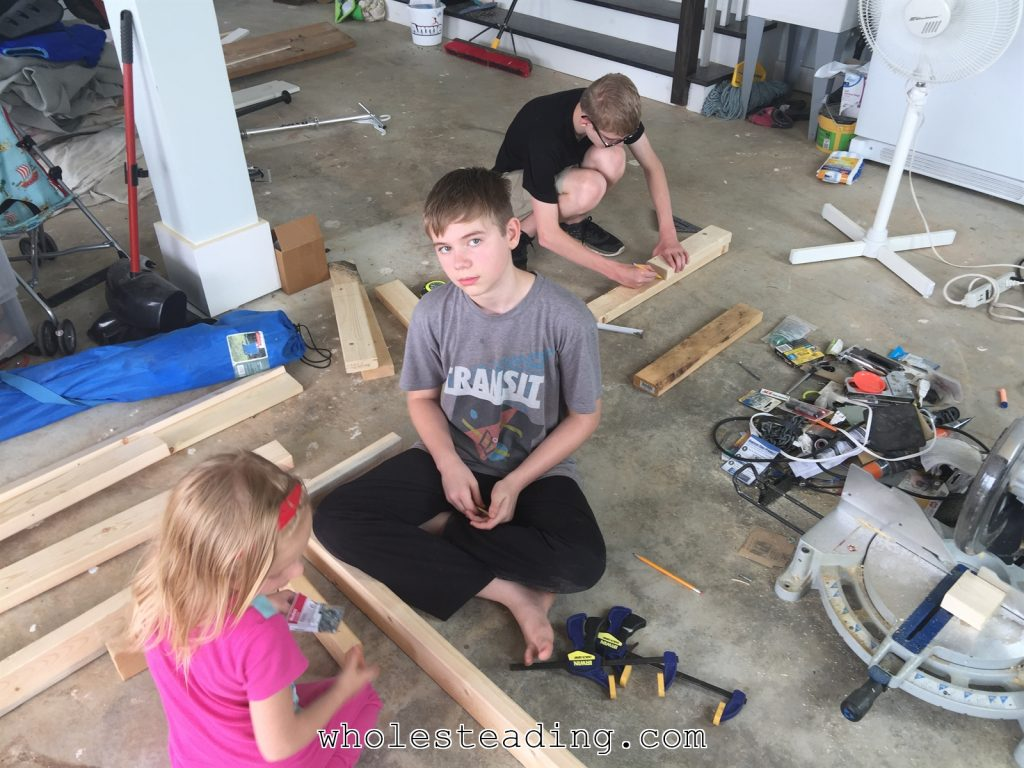 The kids helped with almost every step. Canaan is measuring and making the cuts and Harvest and Noble are putting the washers on the screws and starting them in the pilot holes